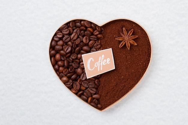 Декоративное кофейное сердце из зерен и растворимого кофе. белая изолированная поверхность.