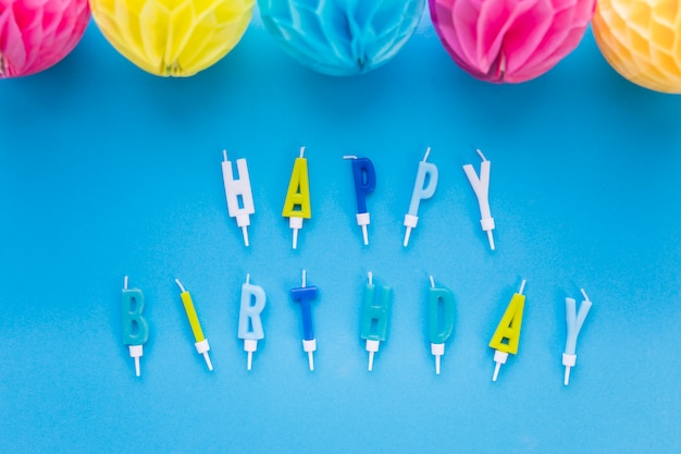 Decorative colorful paper balls and happy birthday text candles on blue background