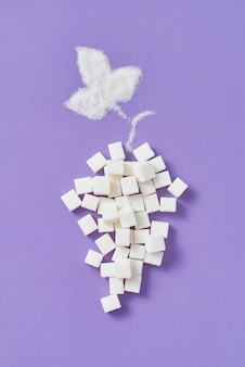 Decorative composition from grape fruit handmade from different types of sweet sugar refined cubes and leaf from granulated sugar on a lavender wall, copy space. flat lay.