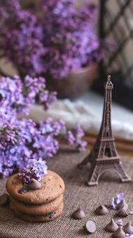Decorative composition with a bouquet of lilacs in a light kitchen interior clay cup of tea and chocolate cake a bouquet of lilacs in a vase spring floral background with lilacs aesthetics