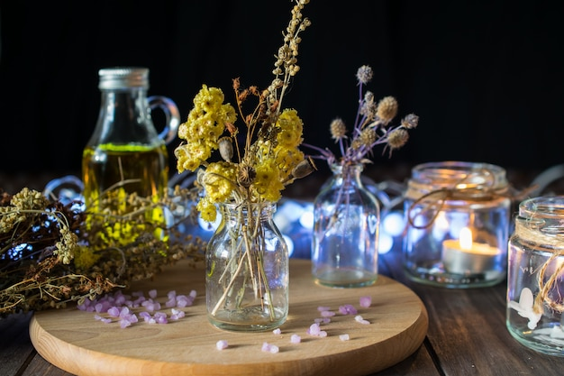 Decorative composition with dried herbs in small glass bottles