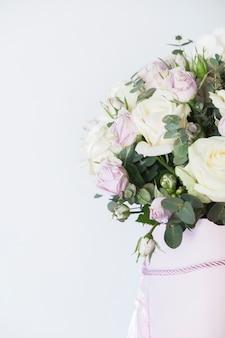 Декоративная композиция со свежими розами на белом фоне