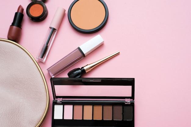淡いピンクの背景にピンクの化粧品バッグから装飾的な化粧品セット