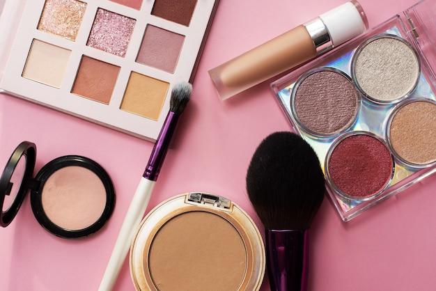 ピンクの背景に装飾的な化粧品セット。コピースペース。メイクアップアーティストのエステティシャン。