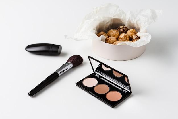 Декоративная косметика и шоколад на белой поверхности
