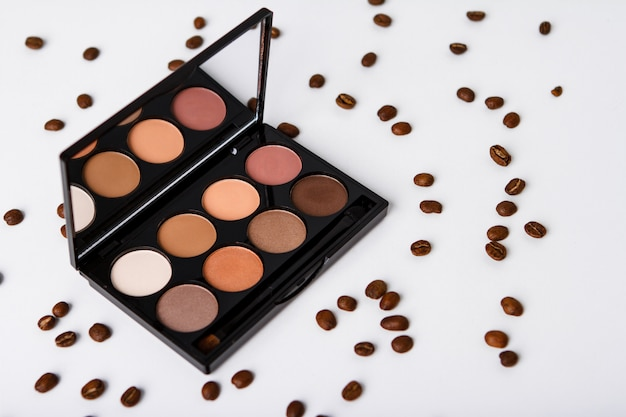 Decorative cosmetics and coffee beans over white surface