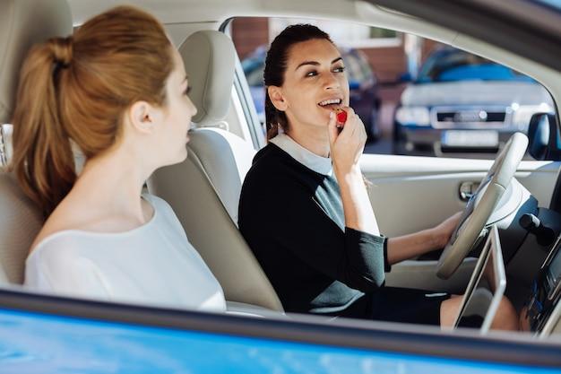 Декоративная косметика. в восторге милая привлекательная бизнесвумен сидит в машине и держит в руке помаду, раскрашивая губы
