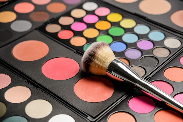 Decorative cosmetics for eye makeup, pallets with bright colors and cosmetic drawing brush