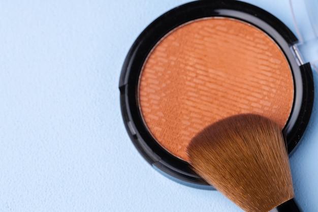 装飾化粧品フェイスパウダーとブラシのクローズアップ写真