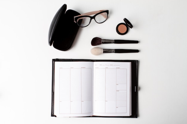 Decorative cosmetics glasses and notebook over white background