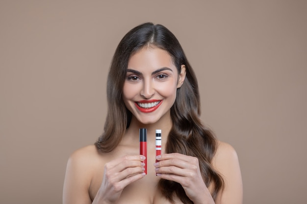 Decorative cosmetics. happy beautiful woman with long brown hair with bare shoulders presenting red lip glosses holding them in front of her