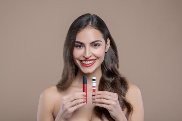 装飾化粧品。彼女の前にそれらを保持している赤いリップグロスを提示する裸の肩を持つ長い茶色の髪を持つ幸せな美しい女性