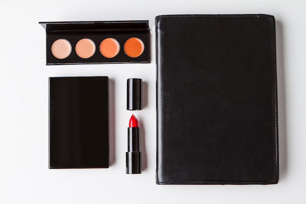 Decorative cosmetics and notebook over white background