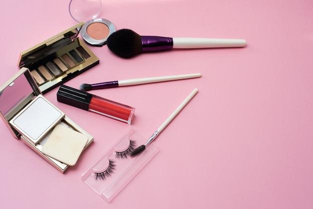 분홍색 배경에 장식 화장품입니다. 밝은 여성용 메이크업을위한 립글로스, 메이크업 브러쉬, 파우더, 아이 섀도우 및 인조 속눈썹. 공간을 복사하십시오.