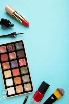 コピースペースと青い背景の装飾的な化粧品。化粧。縦の写真。