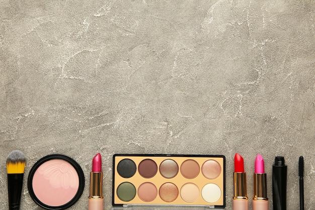 灰色の背景に装飾的な化粧品。化粧。縦の写真。上面図