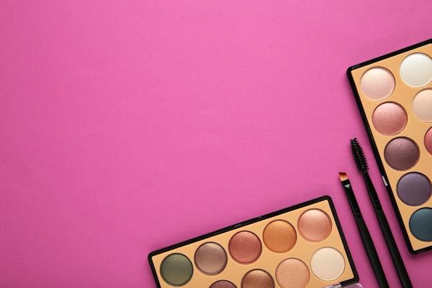 コピースペースとピンクの背景に装飾的な化粧品。化粧。縦の写真。