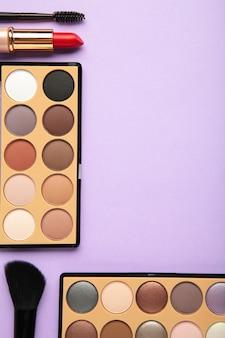 コピースペースと紫色の背景に装飾的な化粧品。化粧。縦の写真。