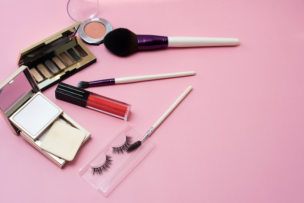 Decorative cosmetics on a pink background. lip gloss, makeup brushes, powder, eyeshadow and false eyelashes for bright lady makeup. copy space.