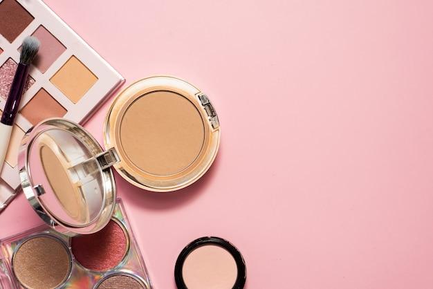 Декоративная косметика. пудра, палитра теней и косметическая кисть для яркого макияжа.