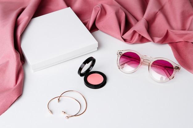 白い表面上の装飾的な化粧品のサングラスとアクセサリー