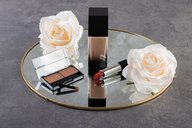 Decorative cosmetics with artificial flowers and mirror on table.