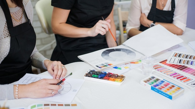 Decorative cosmetology theoretical class. cropped shot of ladies studying colors, using paint and brushes.