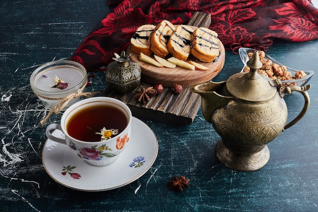 A decorative cup of herbal tea with rollcake slices.