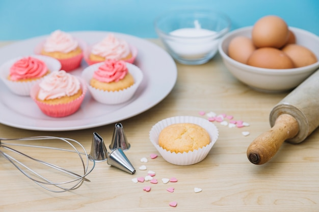 Decorative cupcake with ingredients; whisk; sprinkle; rolling pin and nozzles on wooden desk