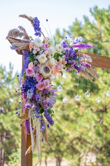 Decorative decoration of the wedding arch with fresh flowers. holding a wedding ceremony in the open. decoration details
