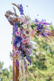 Decorative decoration of the wedding arch with fresh flowers