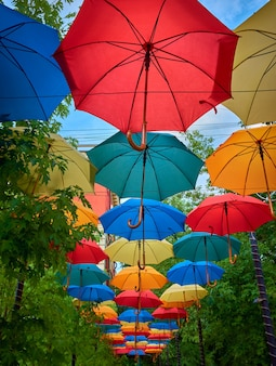 Decorative design of the canopy over the path in the form of opened colorful colored umbrellas