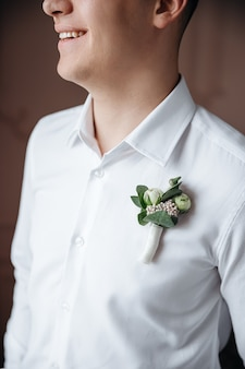 The decorative detail on the shirt of the groom.