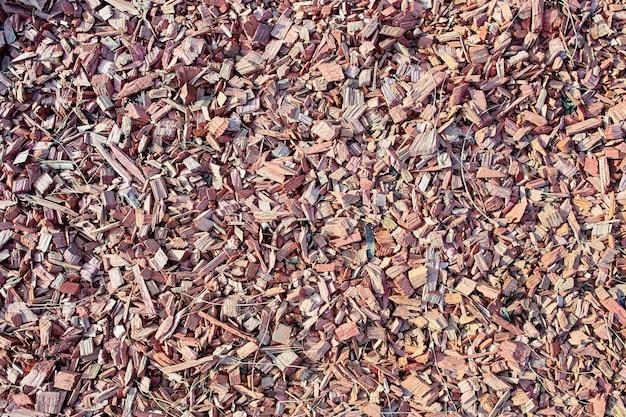 Декоративная отсыпка из древесной щепы для озеленения розовой стружкой на текстуре газона для фона
