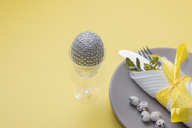 Декоративное пасхальное яйцо в стакане на фоне столовых приборов в тарелке на желтом столе