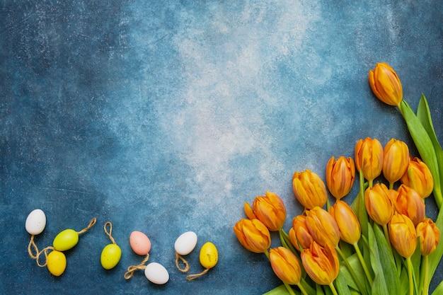 Декоративные пасхальные яйца и весенние тюльпаны на синем фоне. копировать пространство, вид сверху