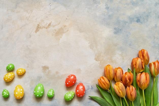 Декоративные пасхальные яйца и весенние тюльпаны на красочном фоне. копирование пространства, вид сверху. плоская планировка концепции празднования пасхи.