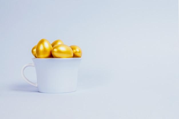 장식용 부활절 달걀은 금색으로 칠해져 있으며 밝은 파란색의 파란색 도자기 컵에 쌓여 있습니다.