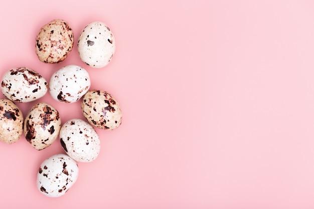 装飾的なイースターエッグ、柔らかいピンクの背景にチョコレート菓子。春休みフラットレイ