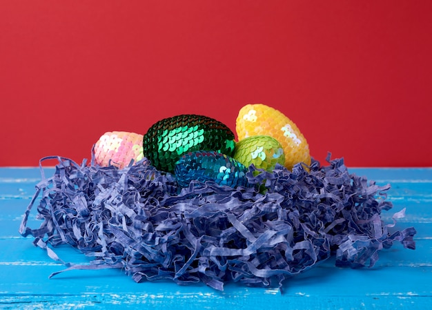 Decorative easter eggs from sequins lie in a nest of strips of paper on a colored surface