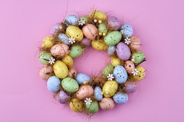 Декоративные пасхальные яйца на розовом фоне. круг из различных разноцветных яиц.