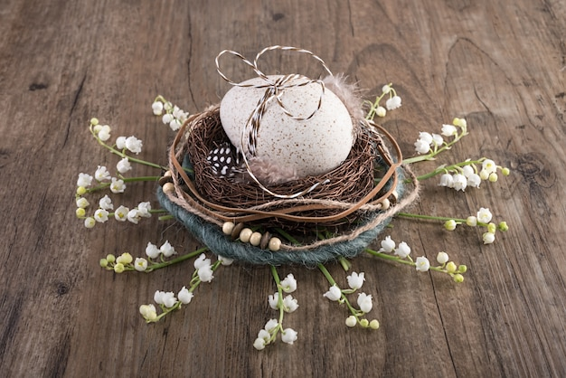 Decorative easter nest on oak table with egg and spring flowers