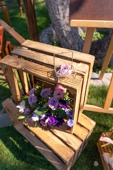 Decorative element from wooden boxes and fresh flowers. details party decoration