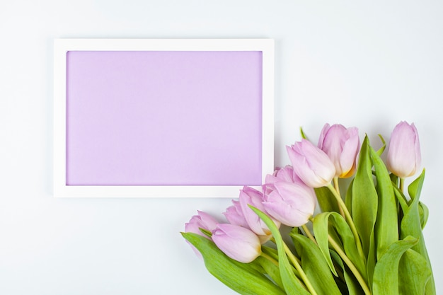 Decorative empty frame with copy space and bouquet of tulips