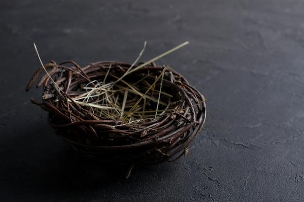 Decorative empty willow birds nest on dark rusty background. copyspace for text