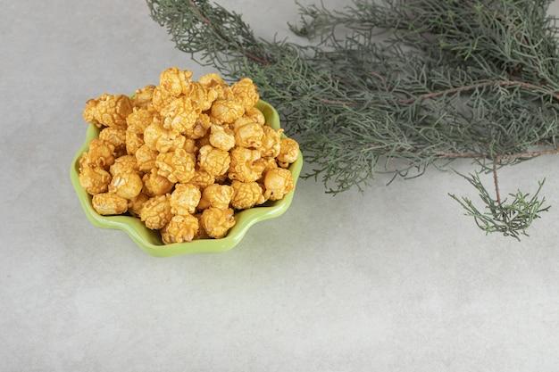 Rami di un albero sempreverde decorativo accanto a una ciotola a forma di fiore verde e caramelle popcorn su marmo.
