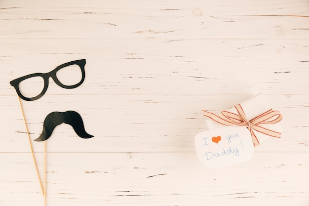 Decorative eyeglasses and moustache near present