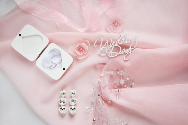 装飾的な生地の花、ホワイトペーパーの背景にピンクのシフォンのブライダルジュエリー