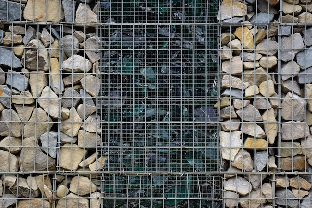 A decorative fence made of stones behind bars and broken large glass in the middle. photographed full frame