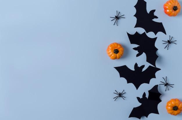装飾的なお祭りの背景ハロウィーン。紙の装飾、コウモリ、クモ、青い背景のカボチャ。コピースペース、フラットレイアウト